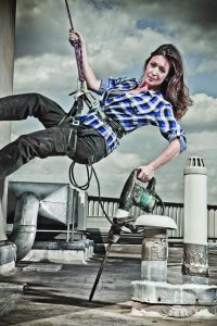 Julia Kendell abseiling with a power drill