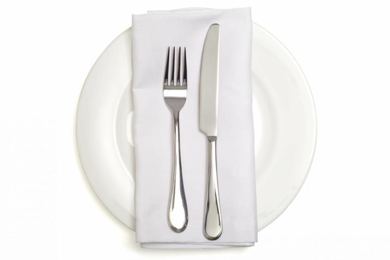 A place setting with silver fork and spoon, white dinner napkin, and white china plate.