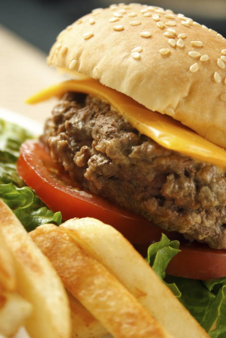 A juicy hamburger on a sesame seed bun with cheese, lettuce, tomato and fries