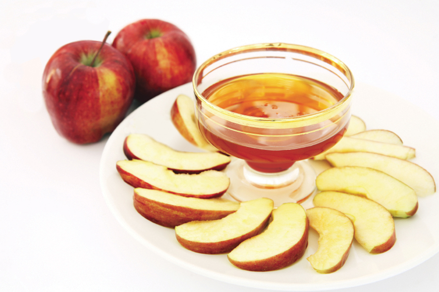 Red delicious variety of apple with a bowl of honey, symbolic of the Jewish New Year.
