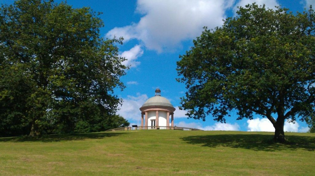 A photograph of a green field and building at Heaton Park, Prestwich