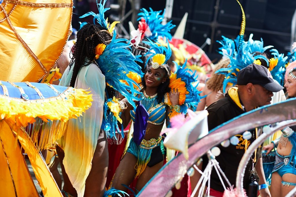 A photo of a costumed participant in the 2017 Leeds Carnival Parade. She is wearing a blue, feathered costume.