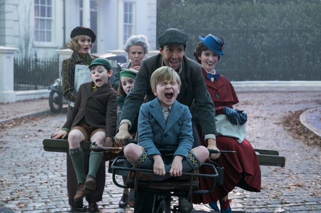 A still from Mary Poppins Returns, showing various characters riding a bicycle