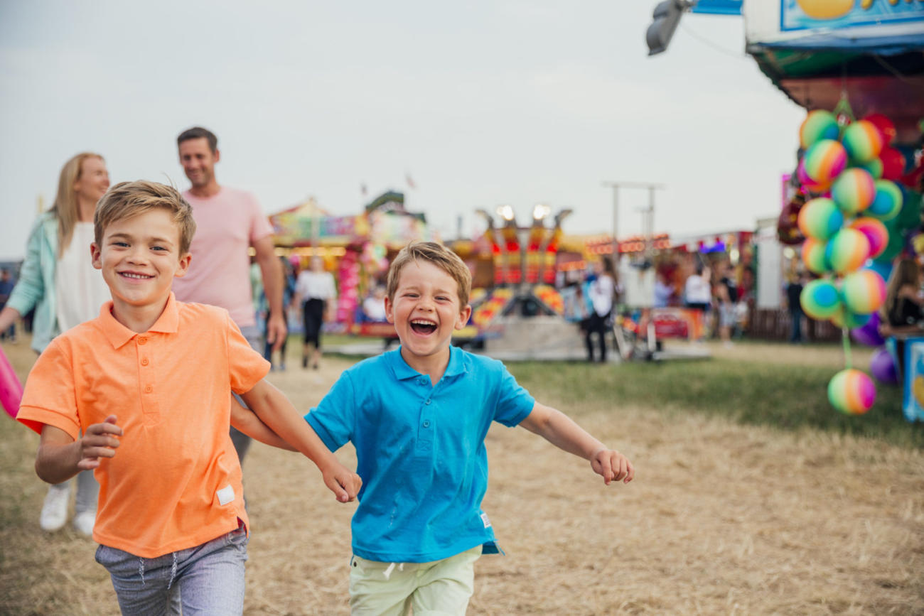 Happy children running ahead of their parents at a fun-fair
