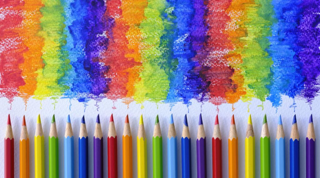 Vibrant rainbow colored water color coloring pencils or crayons in a row standing vertically with corresponding colorful shade drawing background, of the colors blending together, which features behind the crayons. Concept image of people living together in harmony, mixing together, peace etc.