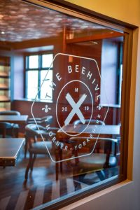 A picture of the window of Matt Healy's restaurant The Beehive, showing its logo