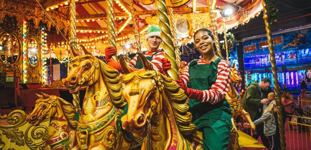 A girl in an elf costume on a carousel at Winter Funland in Manchester