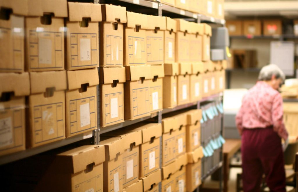An elderly lady stands near the back of a record room at a library.