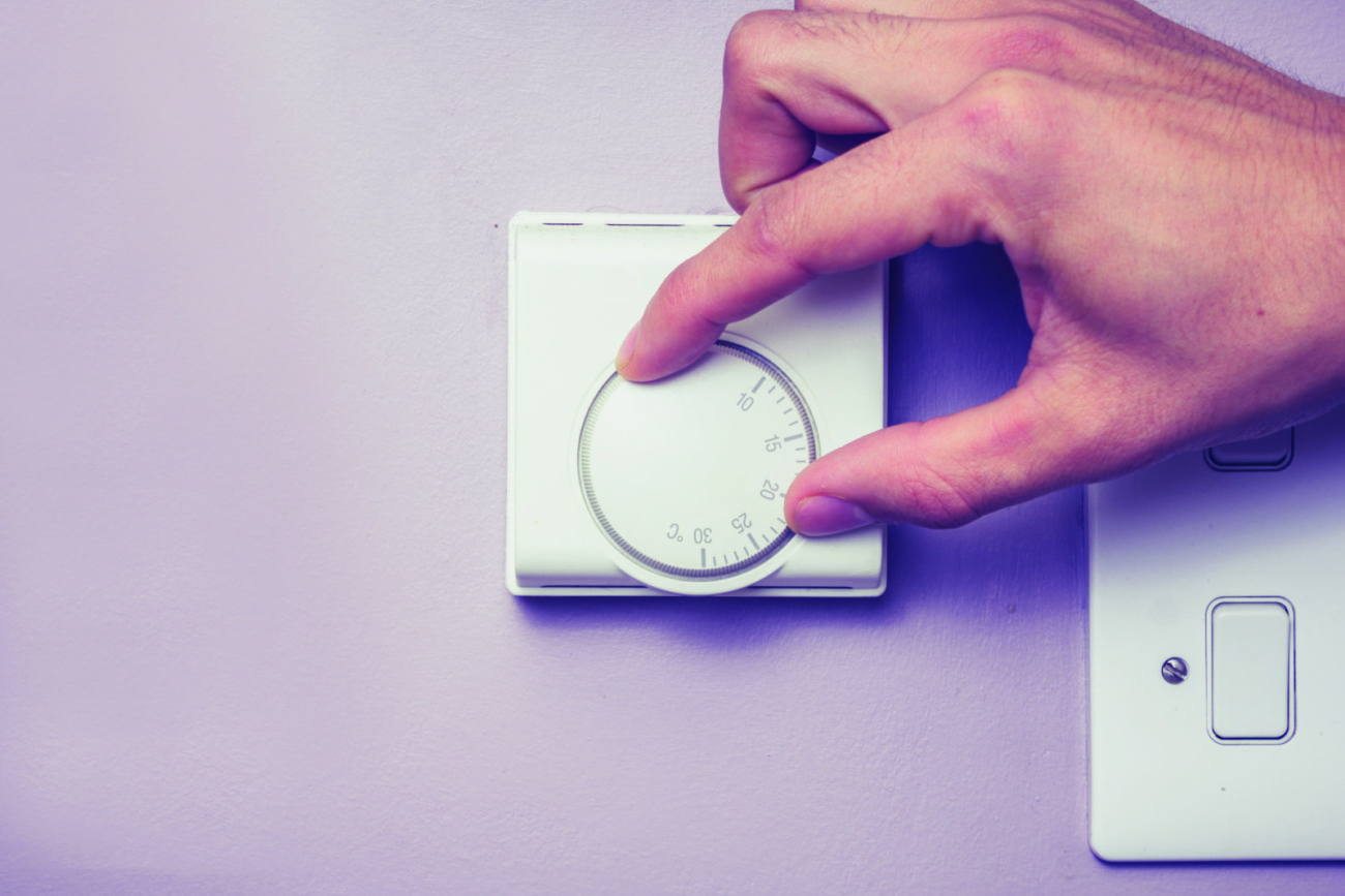 Man's hand turning a dial on a thermostat