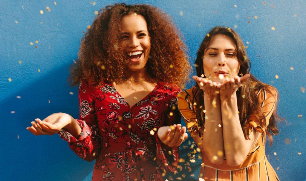 Festive, fashionable women blow glitter at camera