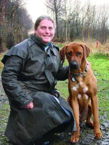 Holly House Vets' dog behaviourist Hazel Shimmin kneels beside dog