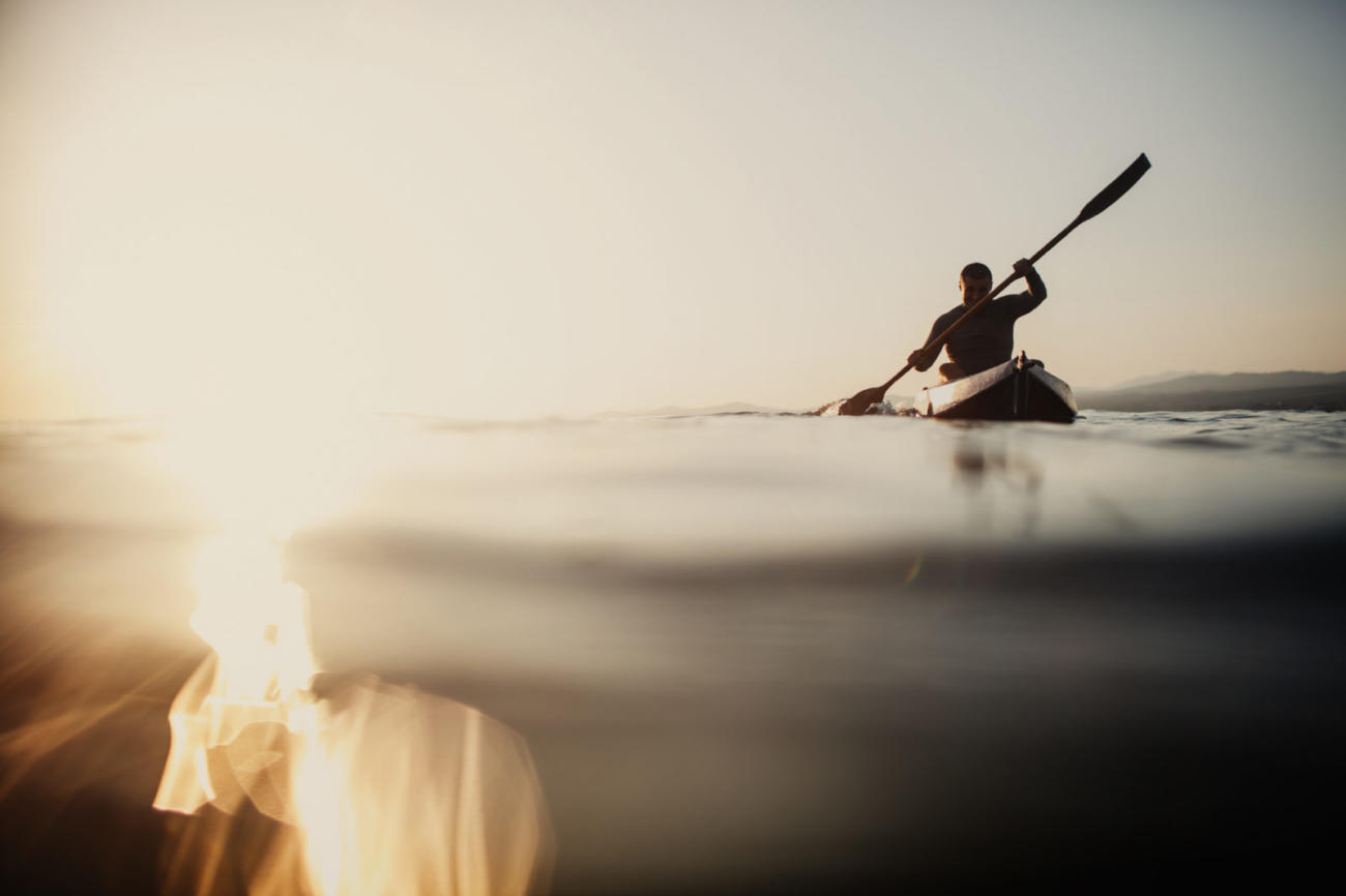 Silhouette of a Man Rowing on Water