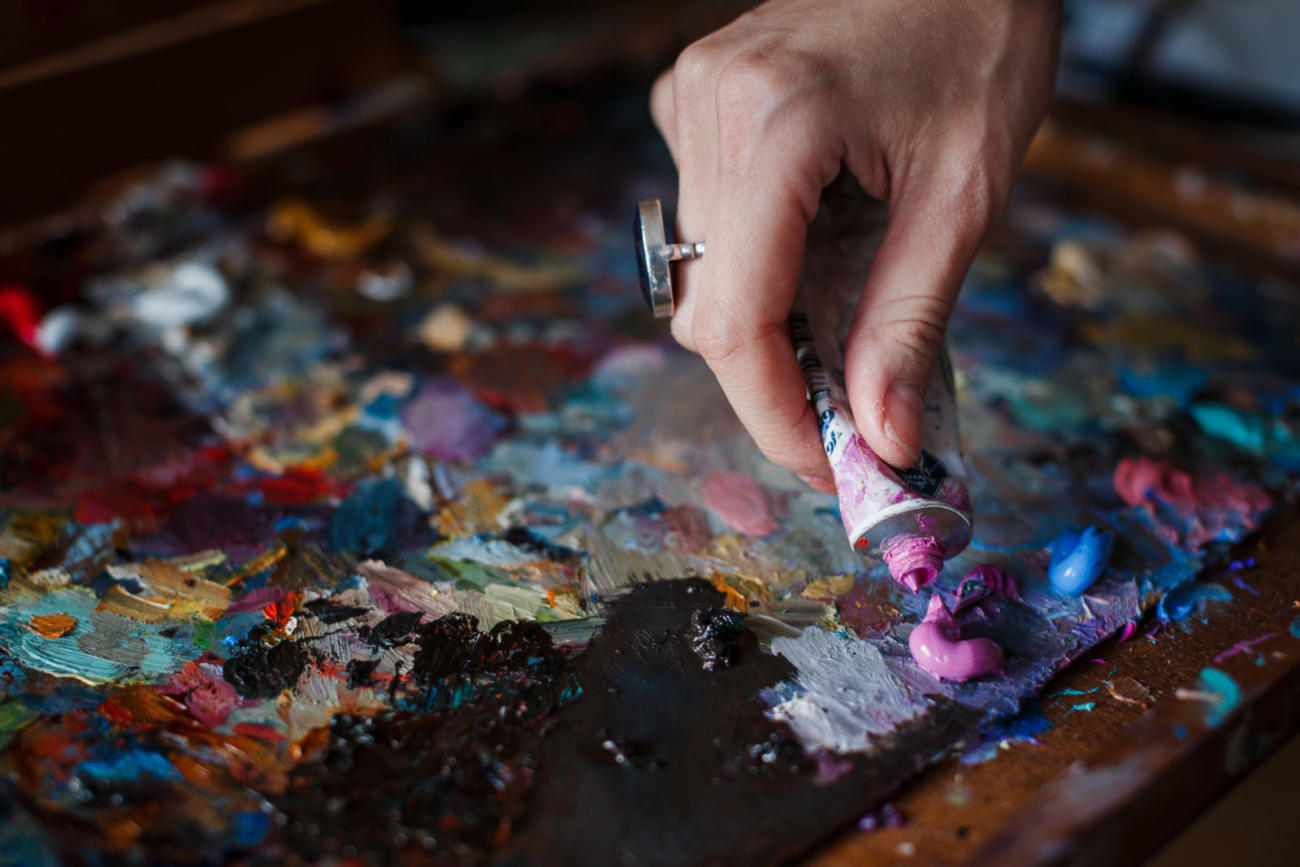 The artist woman squeezes the paint from the tube on the artistic palette. No face. Selective focus.